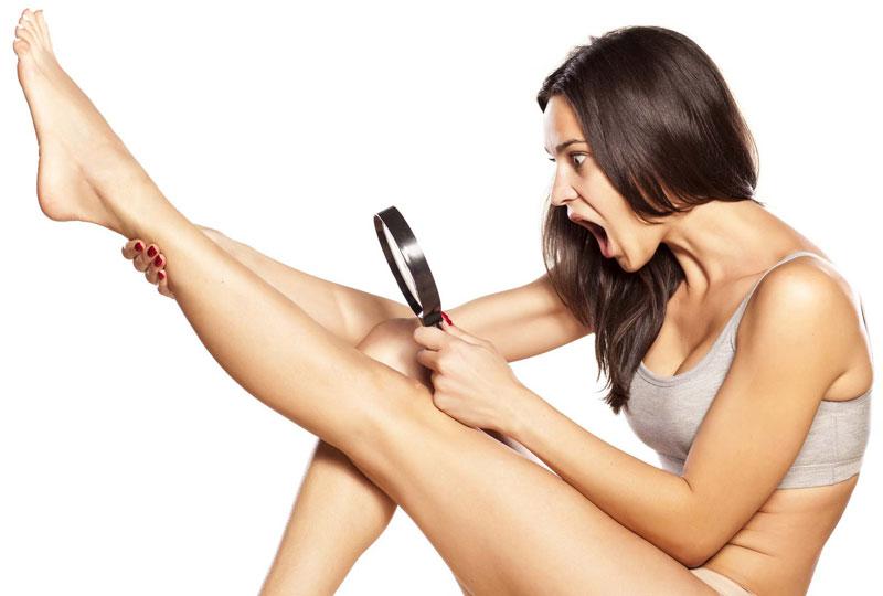 Девушка рассматривает ногу через лупу
