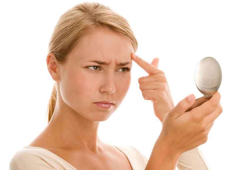 Девушка недовольно смотрится в зеркало