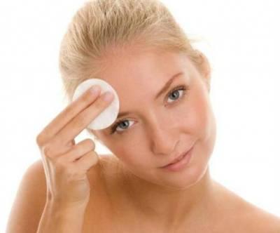 Девушка протирает кожу лица ватным диском