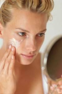 Девушка наносит крем на лицо
