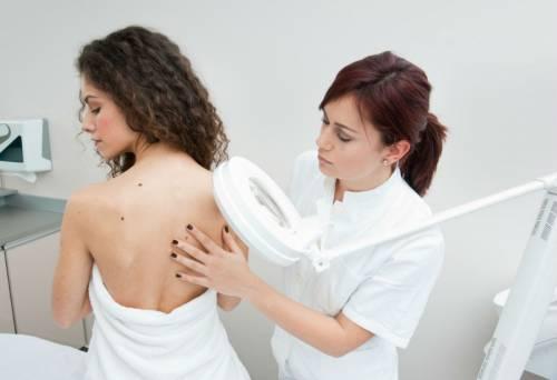 Дерматолог осматривает кожу пациентки
