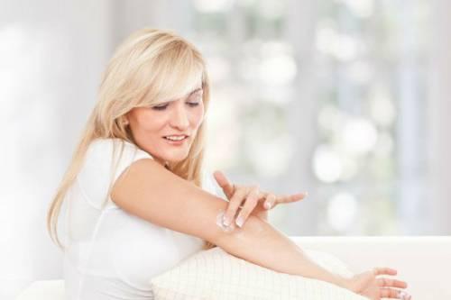 Женщина наносит крем на локти