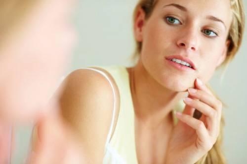 Девушка рассматривает в зеркале лицо