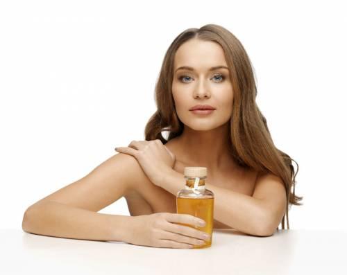 Девушка использует растительное масло для кожи