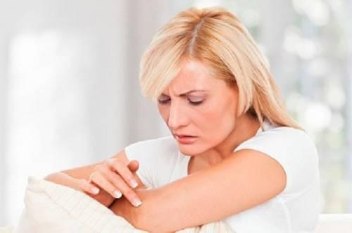 Женщина рассматривает кожу на руке