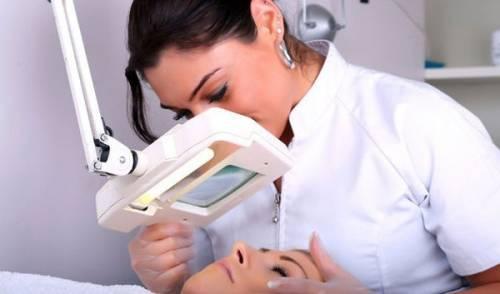 Косметолог осмаривает кожу лица клиентки