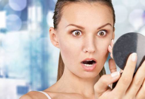 Девушка рассматривает в зеркало лицо