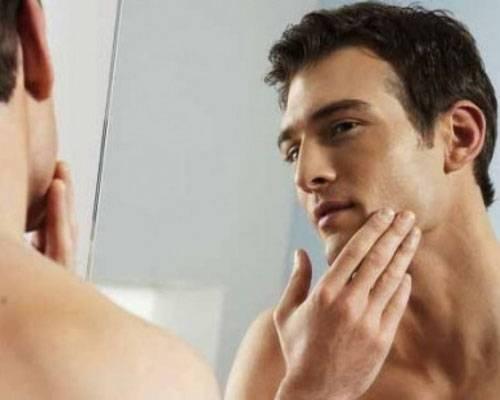 Мужчина разглядывает кожу в зеркало