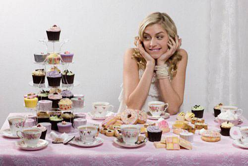 Девушка за стоолм со сладостями