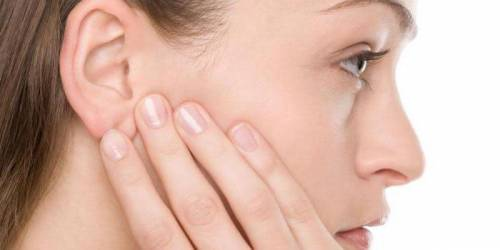Девушка держится рукой за ухо