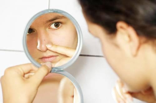 Рассматривание в зеркало образования на лице