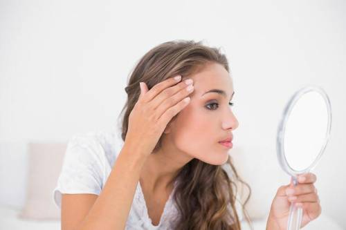 Девушка рассматривает лицо в зеркало