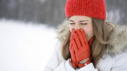 Девушка на морозе закрывает нос руками