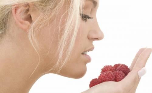 У девушки в руках ягоды малины