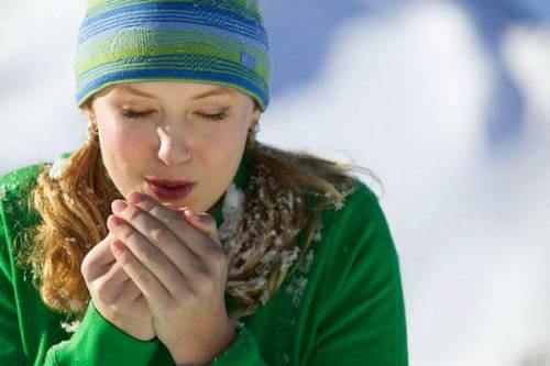 Девушка согревает руки на холоде