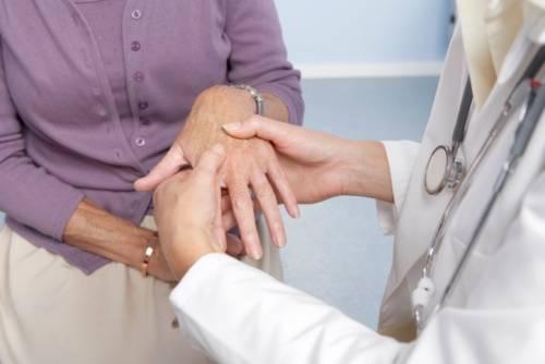 Врач осматривает кисти рук пациента