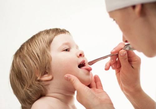 Врач осматривает полость рта ребенка