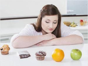 Девушка выбирает между сладостями и фруктами