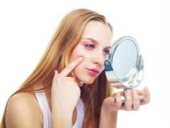 Девушка рассматривает прыщи на лице в зеркале