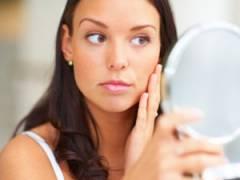 Девушка рассматривает кожу на лице