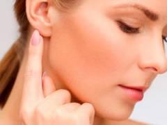 Девушка дотрагивается до уха