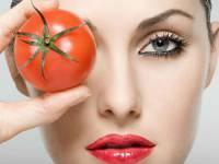 Девушка с красивой кожей держит помидор